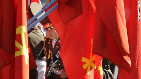 A North Korean soldier peers through flags on display at the Ryomyong residential area.