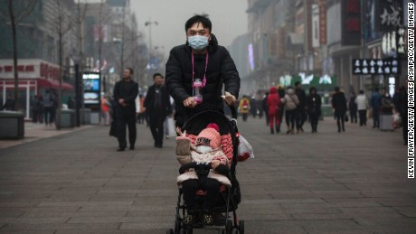 A Chinese man and his son wear masks to protest pollution as they walk through a heavy smog shopping area on December 8, 2015 in Beijing, China.