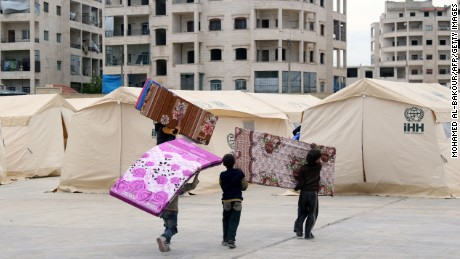 Syrian children prepare mattresses for tents that will house evacuees from Zabadani.