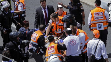 Israeli emergency personnel work at the scene of the stabbing attack Friday in Jerusalem.
