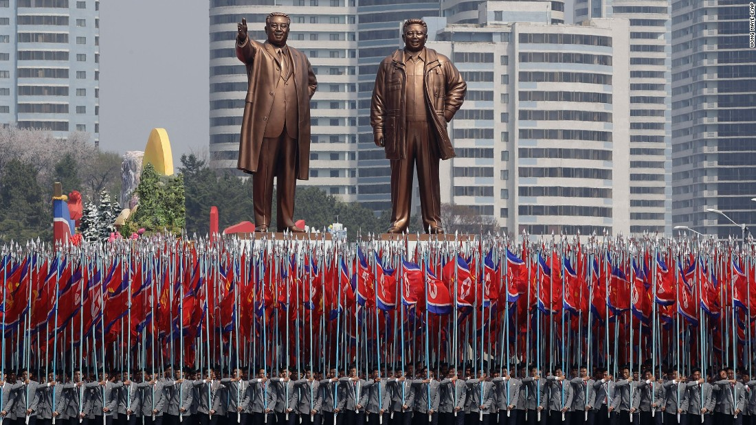 University students carry the national flag and two bronze statues of the late leaders Kim Il Sung and Kim Jong Il.