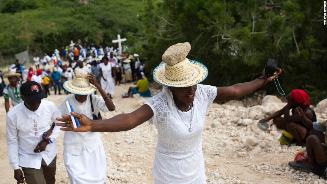 A Haitian woman prays and balances a stone on her head as a form of penance during an annual pilgrimage up the Calcaire Miracle mountain on Good Friday.