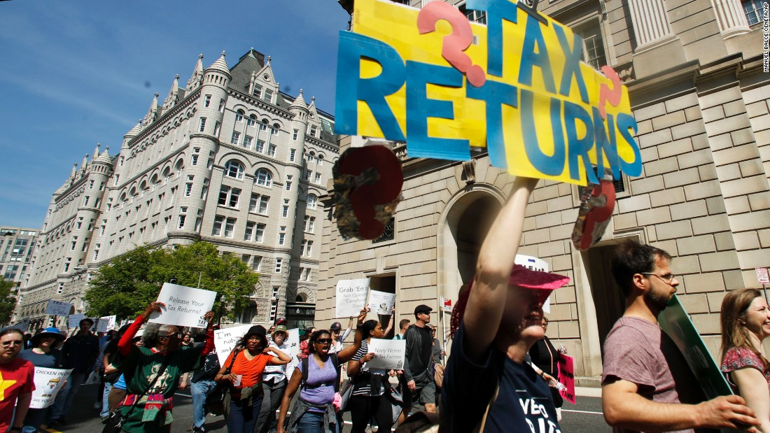 Protesters march past the Trump International Hotel, background left, and the Internal Revenue Services building, right, during a Tax Day demonstration in Washington.