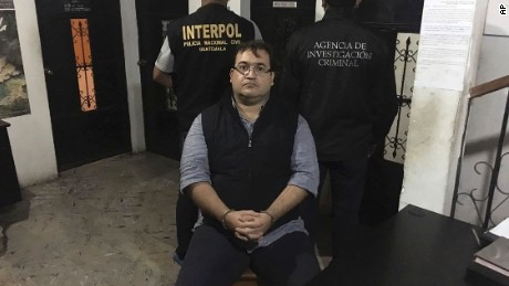In this photo released by the Guatemala National Civil Police (PNC), Mexico's former Veracruz state Gov. Javier Duarte poses for photos escorted by an agent of the Interpol office in Guatemala, left, and a Mexico federal agent at a court room in Panajachel, Guatemala, Saturday, April 15, 2017. Duarte, who is accused of running a corruption ring to pilfer from state coffers, was detained in Guatemala on Saturday. A statement from Mexico's federal Attorney General's Office said Duarte was detained in the municipality of Panajachel, in coordination with Guatemalan police and the local Interpol office. (Guatemala National Civil Police via AP)
