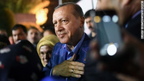 "Turkish president Recep Tayyip Erdogan (C), flanked by his wife Emine Erdogan (rear L), acknowledges supporters, during a rally, as he leaves after delivering a speech at the conservative Justice and Development Party (AKP) headquarters in Istanbul, on April 16, 2017, following the results of a nationwide referendum that will determine Turkey's future destiny. Erdogan on April 16, 2017 hailed Turkey for making a ""historic decision"" as he claimed victory in the referendum on a new constitution expanding his powers. The ""Yes"" campaign to give Turkish President expanded powers won with 51.3 percent of the vote a tightly-contested referendum although the ""No"" camp had closed the gap, according to initial results. But Turkey's two main opposition parties said they would challenge the results. / AFP PHOTO / Bulent Kilic        (Photo credit should read BULENT KILIC/AFP/Getty Images)"