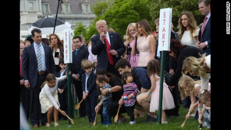 President Donald Trump and first lady Melania Trump, along with members of the first family, blow whistles to begin an Easter Egg Roll race on the South Lawn of the White House in Washington, Monday, April 17, 2017.