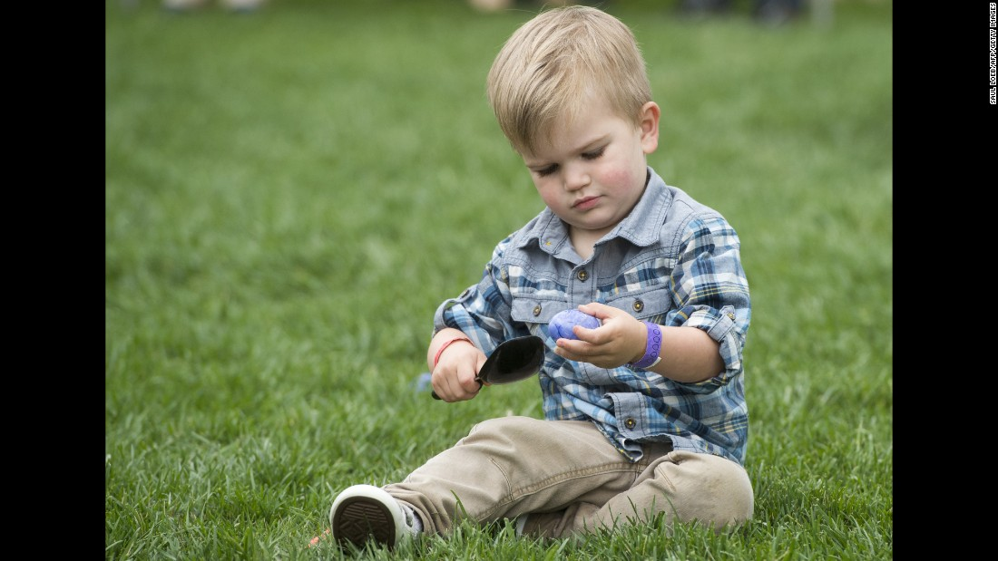 A young boy plays with an Easter egg on the South Lawn of the White House.