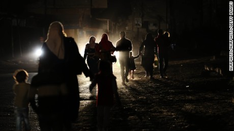 Gazans walk along a darkened street during a power outage on April 14.
