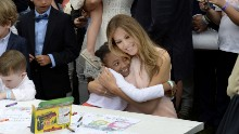 "The first lady hugs a child at the annual <a href=""http://www.cnn.com/2017/04/17/politics/white-house-easter-egg-roll/"" target=""_blank"">White House Easter Egg Roll</a> on Monday, April 17. They were making cards for members of the US military."
