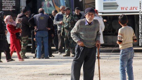 An elderly man waits to board the convoy.