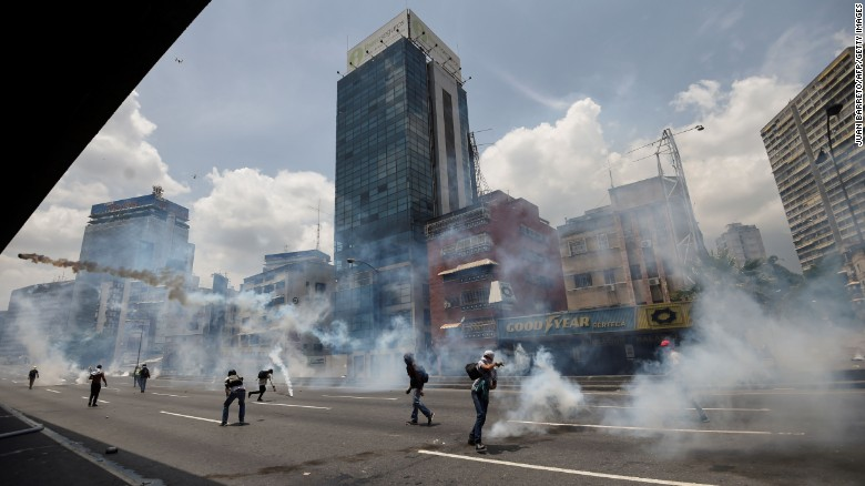Demonstrators clash with the police during a rally against Venezuelan President Nicolas Maduro, in Caracas on April 19, 2017. Venezuela braced for rival demonstrations Wednesday for and against President Nicolas Maduro, whose push to tighten his grip on power has triggered waves of deadly unrest that have escalated the country's political and economic crisis. / AFP PHOTO / Juan BARRETO        (Photo credit should read JUAN BARRETO/AFP/Getty Images)