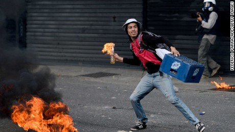 A demonstrator prepares to throw a Molotov cocktail at riot police during a march against Venezuelan President Nicolas Maduro, in Caracas on April 19, 2017.