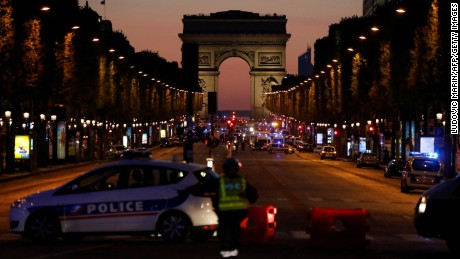 TOPSHOT - Police officers block the access to the Champs Elysees near the Arc de Triomphe in Paris after a shooting on April 20, 2017.