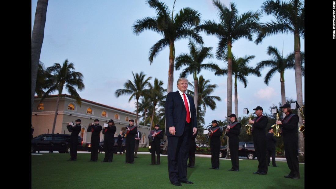 Trump listens to a high school marching band as he arrives at the Trump International Golf Club in West Palm Beach, Florida, on Sunday, February 5. The President and first lady attended a Super Bowl party there.
