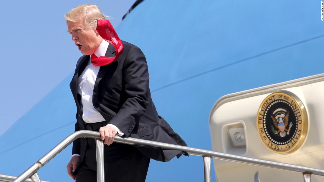 "A strong wind blows Trump's tie as he arrives at Orlando International Airport on March 3. <a href=""http://www.cnn.com/videos/politics/2017/02/02/trump-tie-too-long-moos-pkg-erin.cnn"" target=""_blank"">CNN's Jeanne Moos reports on Trump's presidential neckwear: Long ties with Scotch tape on the back</a>"