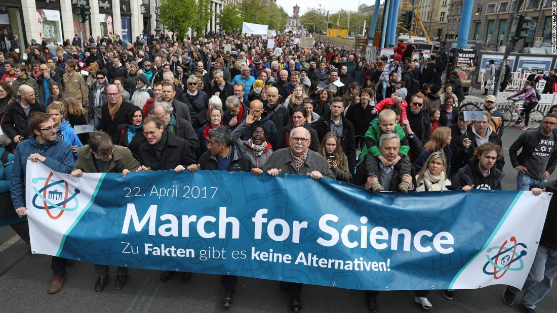 "People show support of scientific research in Berlin, Germany, residents march behind a sign that reads, ""There are no alternatives to facts."""