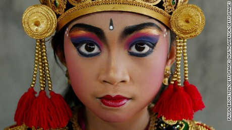 A Balinese dancer poses in her traditional costume before a performance. Music, dance and drama are all closely related in Bali and are essential part of the colorful Balinese culture. Legong dance is the center of classical female Balinese dancing, incorporating no less than 92 movements.