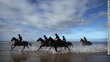 BLACKPOOL, ENGLAND - SEPTEMBER 16:  Gunners and horses of The Kings Troop Royal Artillery cool  off in the surf after a gallop along the beach during their annual holiday break in the seaside resort of Blackpool on September 16, 2009 in Blackpool, England. The horses and gunners of Left Section, The King?s Troop Royal Horse Artillery, are taking a break for their usual ceremonial duties in central London to enjoy a short holiday in Blackpool.  They are guests of the World Horse Welfare's stables at Penny Farm.  (Photo by Christopher Furlong/Getty Images)