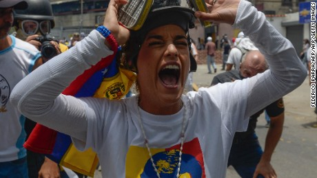 TOPSHOT - Lilian Tintori, wife of jailed Venezuelan opposition leader Leopoldo Lopez, gestures during a protest against Venezuelan President Nicolas Maduro, in Caracas on April 19, 2017. Venezuela braced for rival demonstrations Wednesday for and against President Nicolas Maduro, whose push to tighten his grip on power has triggered waves of deadly unrest that have escalated the country's political and economic crisis. / AFP PHOTO / FEDERICO PARRA        (Photo credit should read FEDERICO PARRA/AFP/Getty Images)