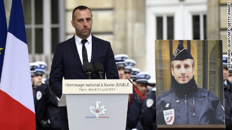 Etienne Cardiles, the partner of Xavier Jugele, the policeman (portrait) killed by a jihadist in an attack on the Champs Elysees, gives a speech during a ceremony to pay tribute to him on April 25, 2017 at the Paris prefecture building.