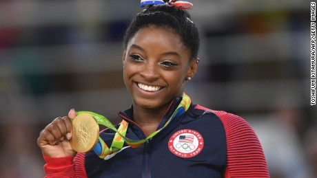 US gymnast Simone Biles celebrates on the podium of the women's floor event final of the Artistic Gymnastics at the Olympic Arena during the Rio 2016 Olympic Games in Rio de Janeiro on August 16, 2016.
