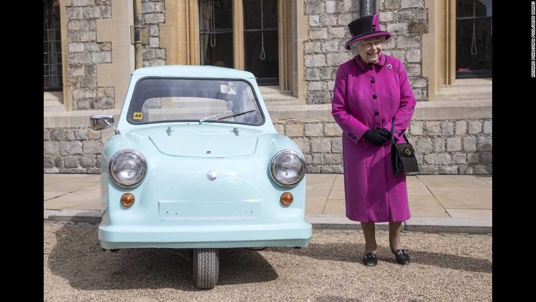"Britain's Queen Elizabeth II stands next to a classic invalid carriage during a ceremony in Windsor, England, on Tuesday, April 25. The invalid carriage -- or ""blue trike,"" as it was known by in the 1960s and '70s -- was a subsidized, low-cost vehicle used by disabled people in the United Kingdom."