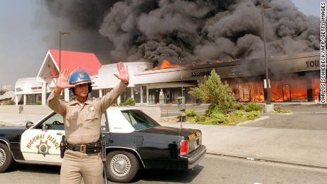 A California Highway patrolman directs raffic around a shopping center engulfed in flames in Los Angeles, 30 April 1992. Riots broke out in Los Angeles, 29 April 1992, after a jury acquitted four police officers accused of beating a black youth, Rodney King, in 1991, hours after the verdict was announced.        (Photo credit should read CARLOS SCHIEBECK/AFP/Getty Images)