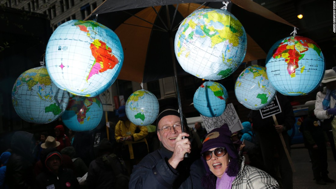 Demonstrators stand under an umbrella with plastic globes during the march in Chicago.