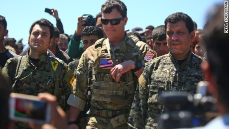 An officer, from the US-led coalition stands alongside Kurdish fighters from the People's Protection Units (YPG) at the site of Turkish airstrikes on YPG positions in Syria.