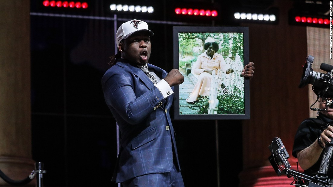 "Takkarist McKinley holds up a photo of his late grandmother, Myrtle Collins, after he was selected by Atlanta in the NFL Draft on Thursday, April 27. ""I told her, before she passed away, I was going to live my dream,"" McKinley said during a passionate interview with NFL Network."