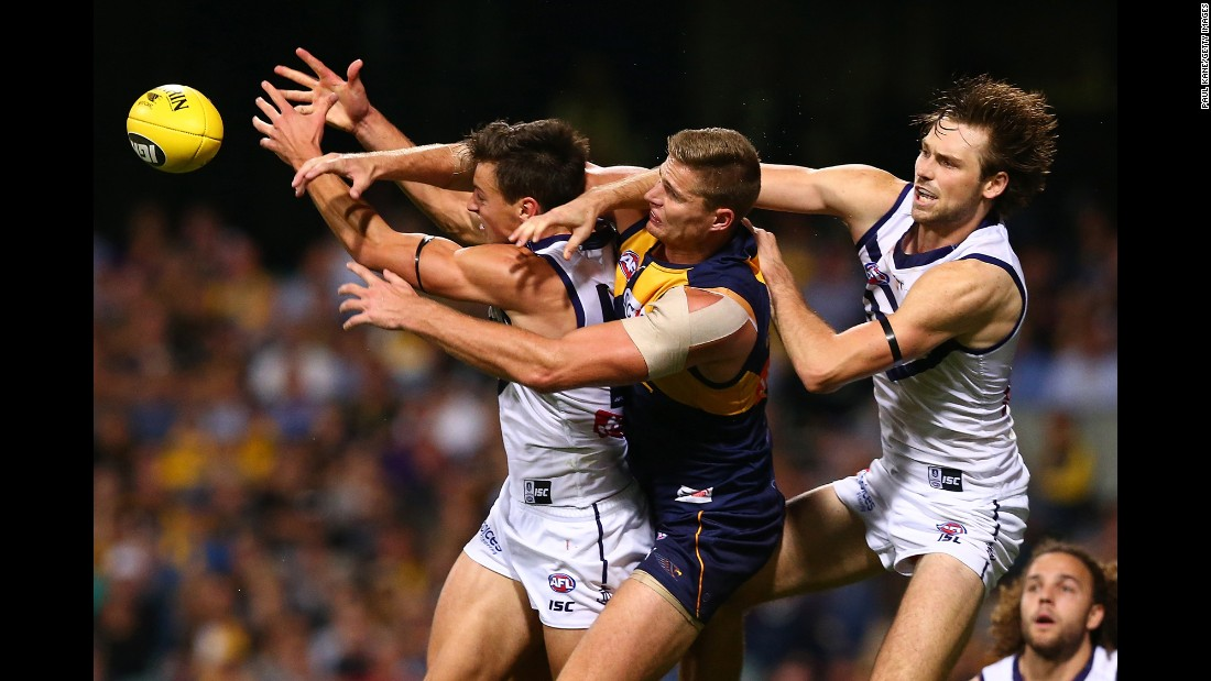 Players compete for the ball during an Australian Football League match in Perth on Saturday, April 29. From left are Fremantle's Ethan Hughes, West Coast's Nathan Vardy and Fremantle's Joel Hamling.