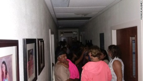 Parishioners shelter inside a hallway at St. John the Evangelist Catholic Church in Emory.