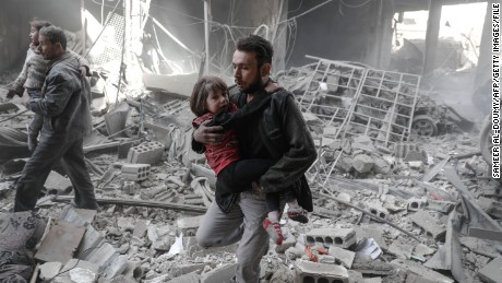 Syrians evacuate children from rubble after February airstrikes on the rebel-held town of Douma.