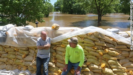 Homeowner Tom Bell, 71, left, and his friend Stan Erlinger take a break from sandbagging and flood preparation on Tuesday in Fenton, Missouri.