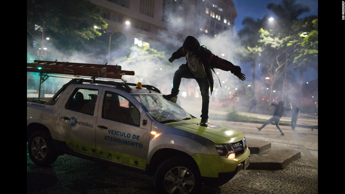 A demonstrator in Rio de Janeiro breaks the windshield of a truck Friday, April 28, after clashes broke out with police during a general strike. Public transport largely came to a halt across much of Brazil on Friday, and demonstrators blocked roads and scuffled with police as part of the strike, which protests proposed changes to labor laws and the pension system.