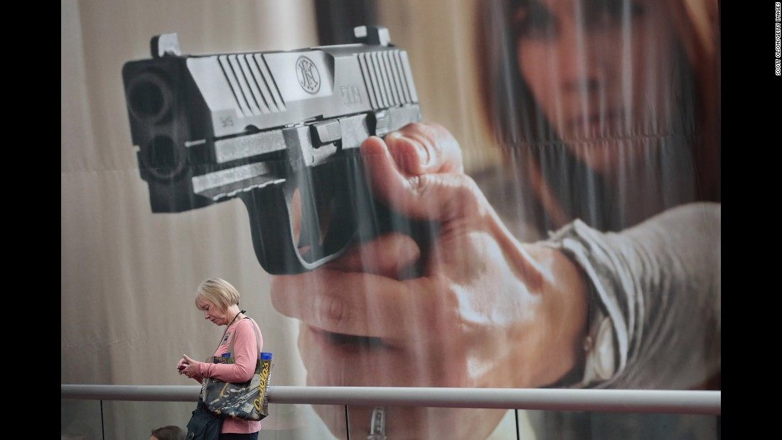 "A woman walks by a large poster at the annual convention of the National Rifle Association on Saturday, April 29. The convention took place in Atlanta this year. <a href=""http://www.cnn.com/interactive/2017/04/politics/nra-convention-cnnphotos/"" target=""_blank"">Related story: Inside ""freedom's safest place""</a>"