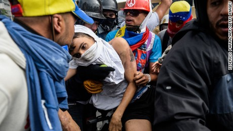 TOPSHOT - An opposition demonstrator ran over by a National Guard control vehicle is dragged away by a fellow demonstrators during a protest against Venezuelan President Nicolas Maduro, in Caracas on May 3, 2017. Venezuela's angry opposition rallied Wednesday vowing huge street protests against President Nicolas Maduro's plan to rewrite the constitution and accusing him of dodging elections to cling to power despite deadly unrest. / AFP PHOTO / FEDERICO PARRA        (Photo credit should read FEDERICO PARRA/AFP/Getty Images)