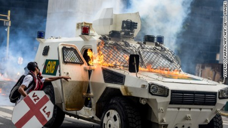 The crew of a blazing riot control vehicle open its hatches upon being hit by Molotov cocktails thrown by opposition activists during a protest against Venezuelan President Nicolas Maduro, in Caracas on May 3, 2017. Venezuelan police fired tear gas and hooded protesters hurled Molotov cocktails as thousands rallied Wednesday in anger at President Nicolas Maduro's plan to rewrite the constitution. At least one protester caught fire and two opposition lawmakers were among various people injured, AFP reporters at the scene said. / AFP PHOTO / FEDERICO PARRA        (Photo credit should read FEDERICO PARRA/AFP/Getty Images)