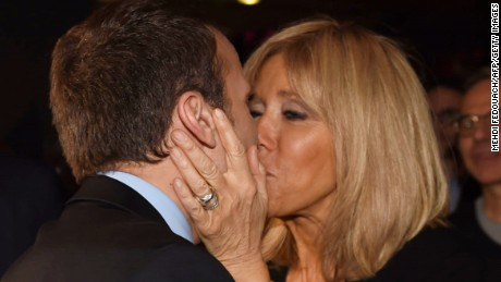 Emmanuel Macron kisses his wife as he arrives for a campaign rally on March 9.