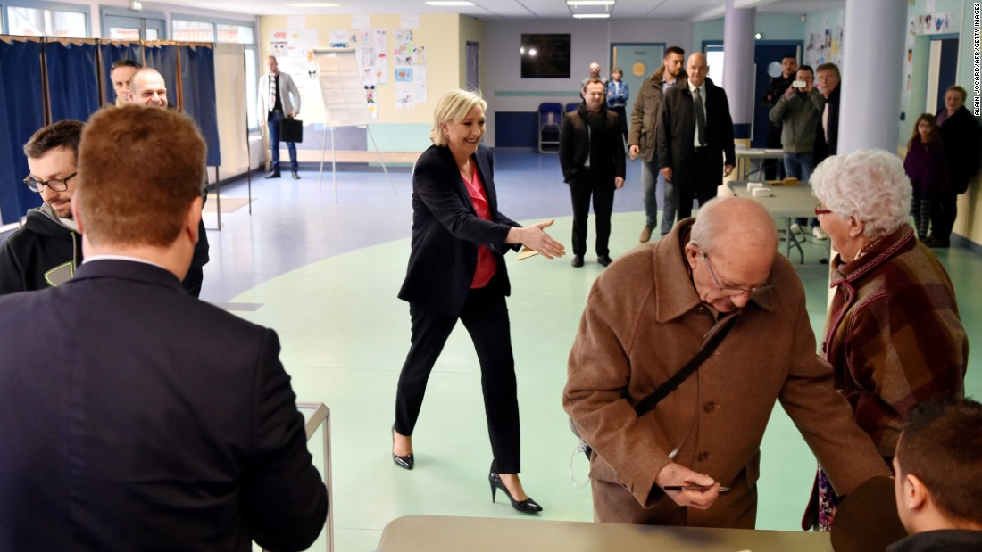 French presidential candidate Marine Le Pen moves to shakes hands with a woman at a polling station in Henin-Beaumont, France, Le Pen's home town.
