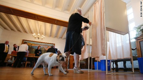A woman with her dog enters a voting booth to cast her ballot in Saint Jean de Luz, France, on Sunday.