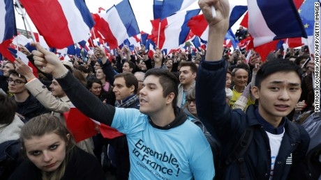 Supporters of the French presidential election candidate for the En Marche ! movement Emmanuel Macron wave French national flags in front of the Pyramid at the Louvre Museum in Paris on May 7, 2017, during the second round of the French presidential election. / AFP PHOTO / Patrick KOVARIK        (Photo credit should read PATRICK KOVARIK/AFP/Getty Images)