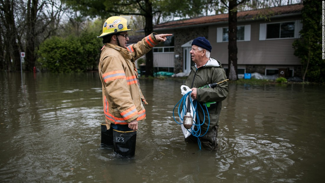 A firefighter speaks to a resident of Quebec's Mercier Island on Saturday, May 6.
