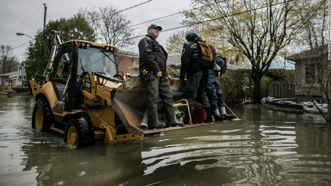 Residents of Mercier Island carry a pump with a tractor on May 6.