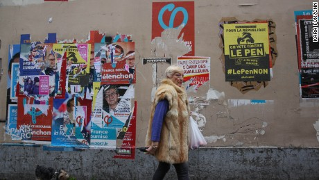 A woman walks past election campaign posters in Paris' 18th district. One poster, in yellow, encourages voters to vote against Marine Le Pen.