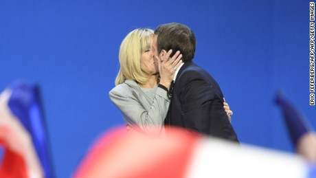 French presidential election candidate for the En Marche ! movement Emmanuel Macron kisses his wife Brigitte Trogneux (L) on stage at the Parc des Expositions in Paris, on April 23, 2017, after the first round of the Presidential election. / AFP PHOTO / ERIC FEFERBERG / ALTERNATIVE CROP         (Photo credit should read ERIC FEFERBERG/AFP/Getty Images)