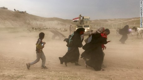 Residents from north west Mosul fleeing fighting between Iraqi security forces and ISIS, during a sand storm carrying few belongings and their children in their arms.