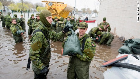 Canadian Forces personnel unload sandbags in Deux-Montagnes, Quebec.