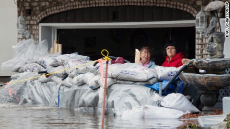Residents look out from their garage over sandbags in Ile Bizard, Quebec.