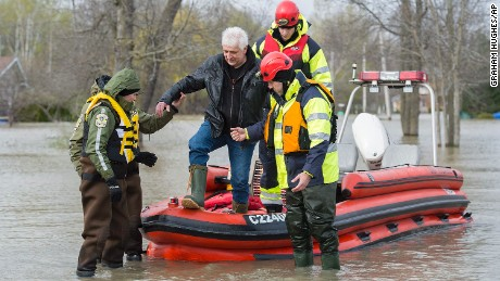 A man is assisted by Surete du Quebec police officers after being evacuated from his home in the town of Rigaud, Quebec.